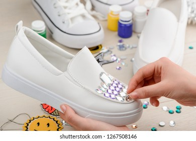 Girl upgrades her shoes with rhinestones. Simple creative DIY ideas, makeover of old shoes.