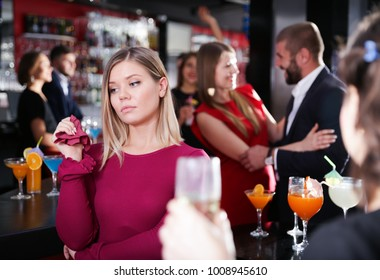 Girl upset because her boyfriend flirting with other woman on Hawaiian party in bar