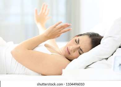 Girl upset waking up with the light bothering her lying on a bed in the morning