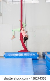 Girl upside down on circus class with blue mattress below