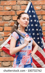 Girl with USA flag and a hammer near the brick wall