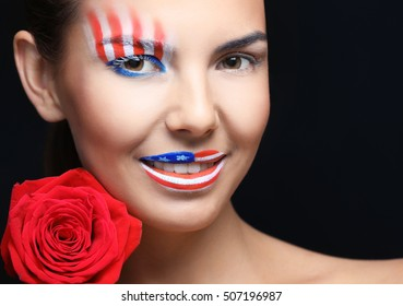Girl with USA makeup and red rose on black background