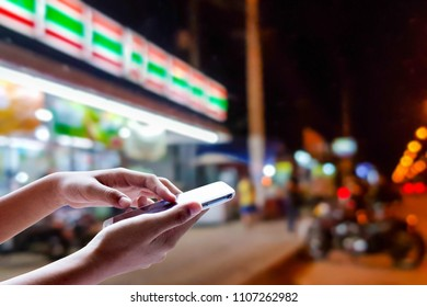 Girl use mobile phone, blur image of the front of the convenience store at night as background.