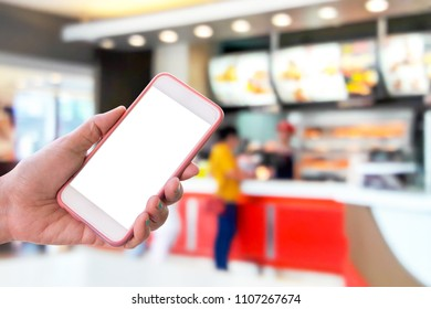 Girl use mobile phone blur image of fast food restaurant as background.