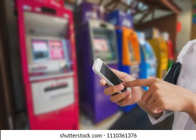 Girl use mobile phone, blur image at ATM machine as background.