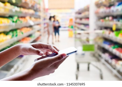 Girl use mobile phone, blur image of customers are shopping in the department store as background.