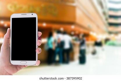 Girl use mobile phone, blur image of reception in hotel as background.