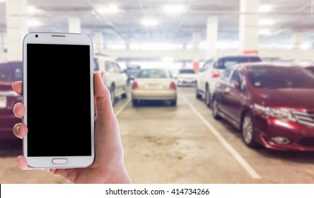 Girl use mobile phone, blur image of  parking inside the mall as background.