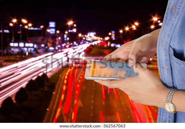 Girl use mobile phone,  blur the light of cars on the road at night as background.