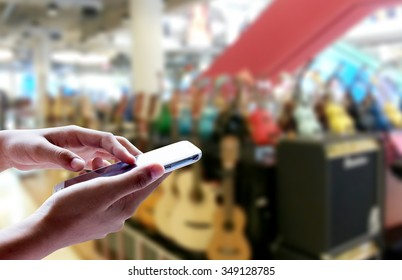 Girl use smart phone, blur image of musical instrument stores as background.