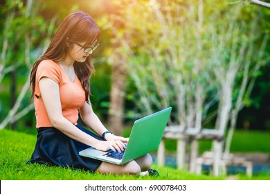 Girl uses a laptop computer in the park. Checking email, message, update her status on the social network.