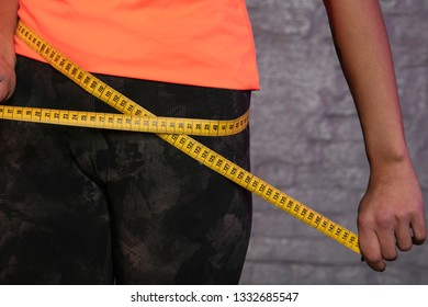 girl uses a measuring cup to measure the body's circumference