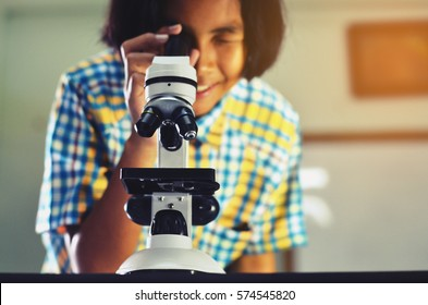 Girl uses a microscope in the school