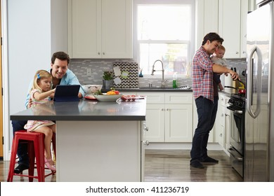 Girl uses tablet in kitchen with dad, while other dad cooks