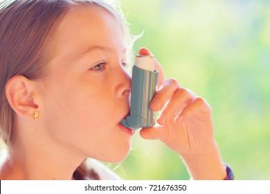 Girl using asthma inhaler in a park - vintage effect filter
