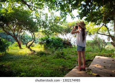 Girl using binoculars in the jungle