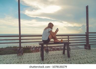 Girl using cellphone on the ocean shore.