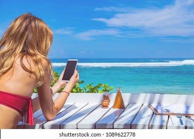 Girl using cellphone in the restaurant on a exotic tropical beach.