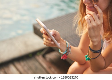 Girl using cellphone while lying on a swimming pool deck lounge bed.
