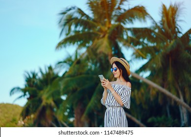 girl using a cellphone while waking along the beach
