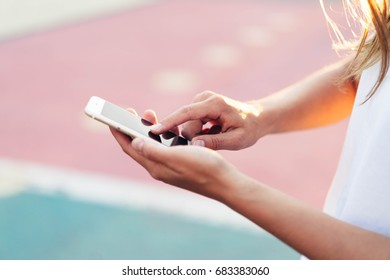 Girl using holding in hands ,mobile phone, hipster pointing finger on smartphone screen, background lightning glow bokeh light