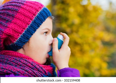 Girl Using Inhaler on an autumn day - to Treat Asthma Attack. Inhalation treatment of respiratory diseases. Shallow depth of field. Allergy concept. Asthma Child.