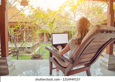 Girl using laptop on a home porch / terrace.