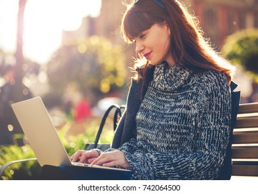 Girl using laptop outdoor sitting in the city street, urban scene