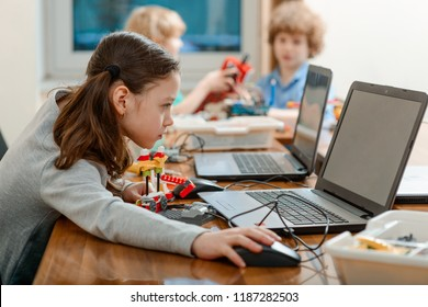 Girl using a laptop while assembling a robot from plastic bricks. STEM Education for kids. - Shutterstock ID 1187282503