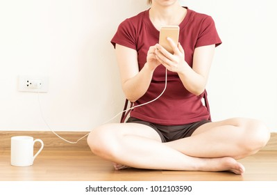 Girl using mobile phone while charging the battery