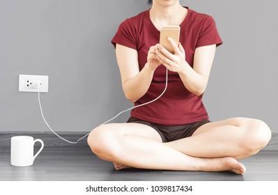 Mädchen, die Mobiltelefon benutzen, während sie den Akku aufladen