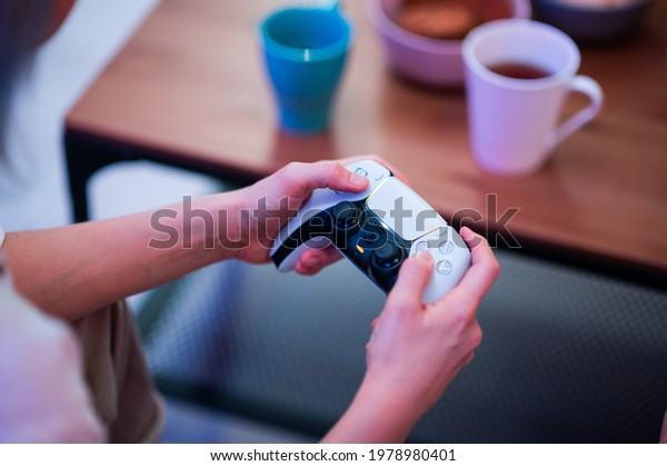 Girl using new Sony Playstation 5 DualSense wireless controller which offers immersive haptic feedback, dynamic adaptive triggers and a built-in microphone. Moscow - November 28 2020.