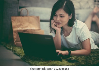 Girl using notebook shopping online at home with vintage color tone