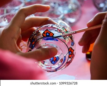 The girl is using a paintbrush painted on a glass. Handicrafts kids activity. Fun training for kids.