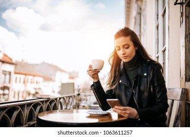 Girl using phone while enjoying a cup of coffee on the balcony over the city street.