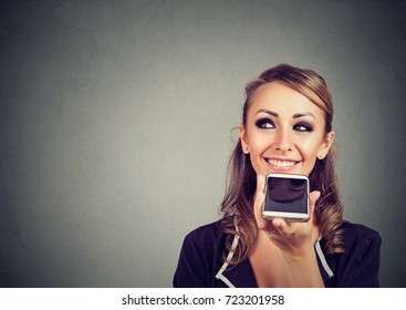 Girl using a smart phone voice recognition function online on gray wall background