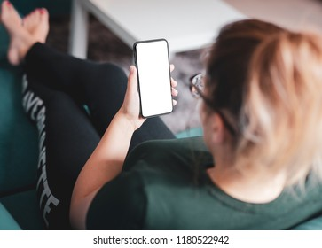 Girl using smartphone with frameless design and blank screen while sitting on sofa in home interior