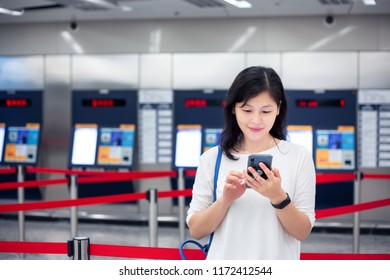 Girl using smartphone in front of ticket vending machine