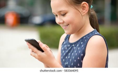 Girl is using smartphone, outdoor shoot