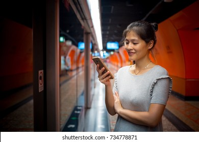 Girl using smartphone in subway station