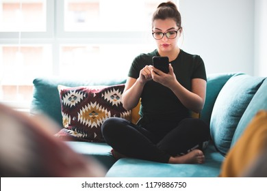 Girl using smartphone while sitting on sofa in home interior
