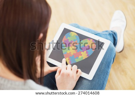 Girl using a tablet pc sitting on the floor against autism awareness heart