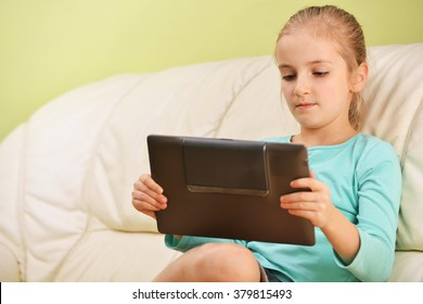 girl using  tablet  sits on couch
