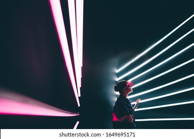 Girl using VR goggles in colorful neon lights, having fun. Wearable virtual augmented reality digital innovation technology concept