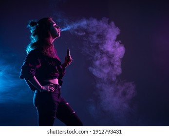 A girl with a VAPE stands in profile. A woman smokes a VAPE and lets out smoke. Girl vaper on a dark background. A girl with an e-cigarette looks at the smoke. Vaping concept with place for text.