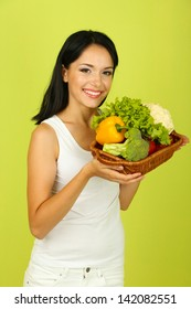 Girl with vegetables on green background