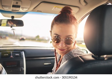 Girl in vehicle with sun shining is looking at the camera