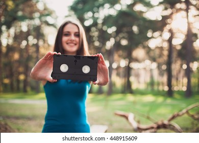 Girl with a VHS cassette in her hands. Blur bokeh