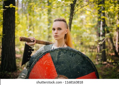Girl Viking in the Mail. Beautiful girl with a gun in her hands and with a round shield. A woman is a warrior in the forest. Medieval image