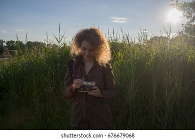 The girl with vintage camera is standing in the grass